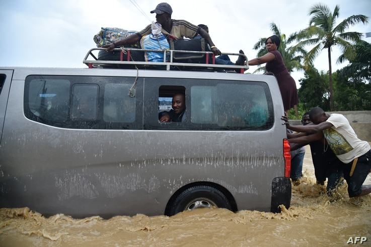 People try to cross the overflowing La Rouyonne river in the commune of Leogane, south of Port-au-Prince, Oct. 5, 2016.