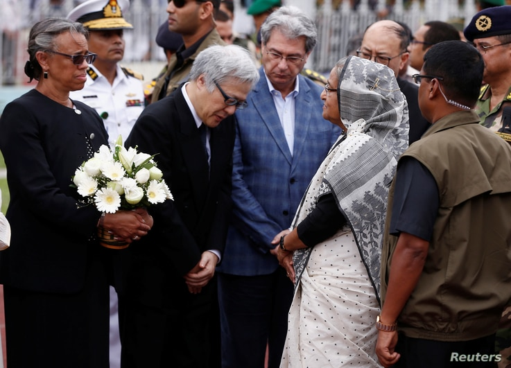 Bangladesh's Prime Minister Sheikh Hasina (2nd R) talks to Japanese ambassador to Bangladesh Masato Watanabe (2nd L) after paying homage to the victims who were killed in the attack on the Holey Artisan Bakery and O'Kitchen Restaurant, during a memor...