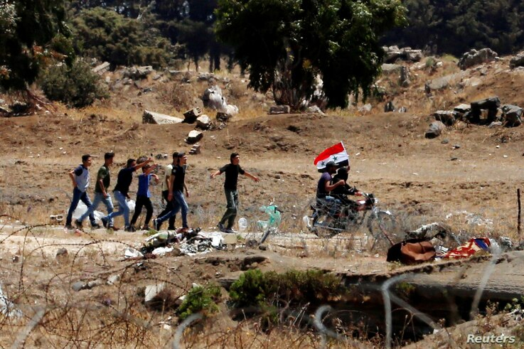 Men ride a motorbike as they carry a Syrian flag in Quneitra on the Syrian side of the cease-fire line between Israel and Syria, as seen from the Israeli-occupied Golan Heights, July 27, 2018.