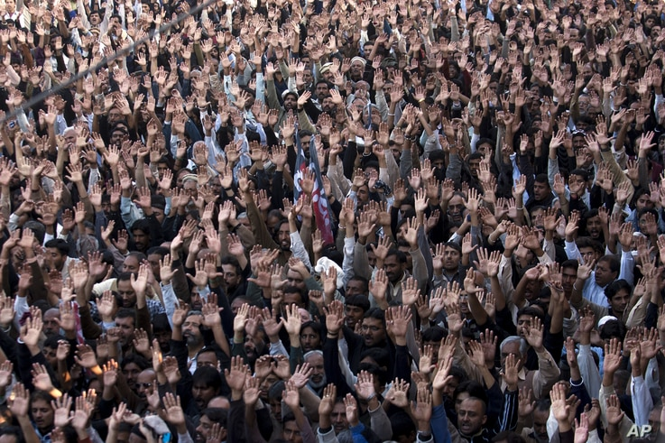 People raise their hands to condemn a suicide attack on Shi'ite mourners during a funeral in Rawalpindi, Pakistan, November 22, 2012.