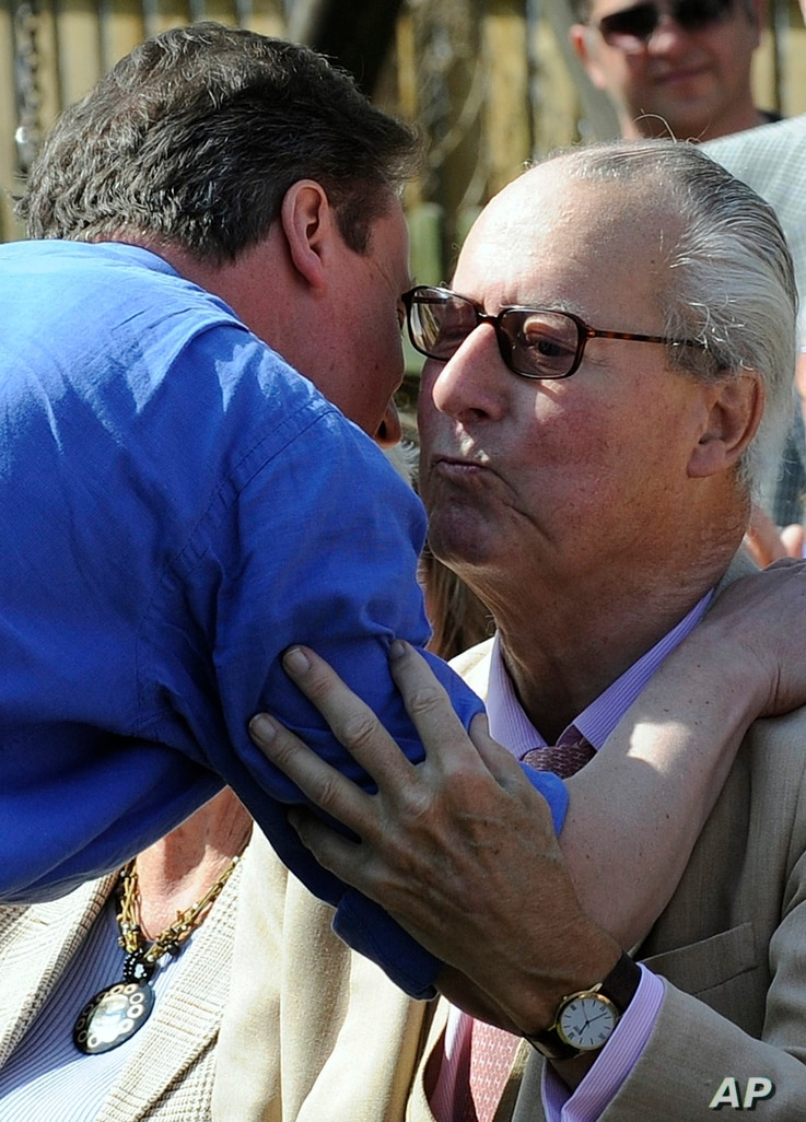 FILE - David Cameron, embraces his father, Ian, before addressing supporters in the garden of a public house in Swindon, south west England, Sunday April 18, 2010.