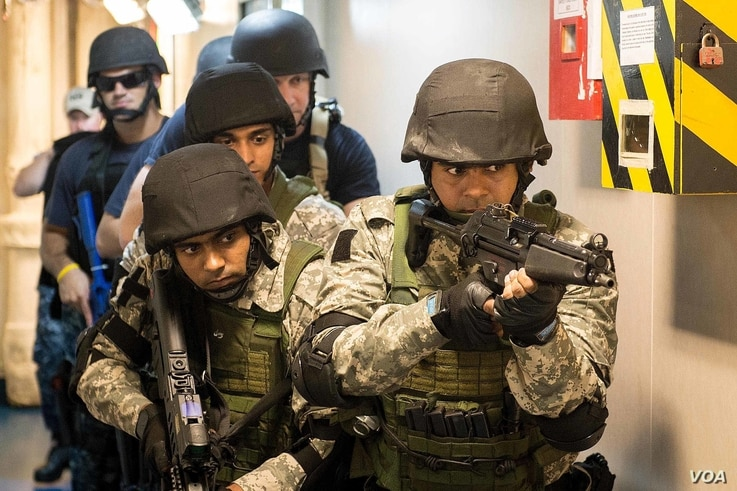 FILE - Team members from the Indian and U.S. navies take part in a joint training exercise aboard an Indian ship in June 2016.