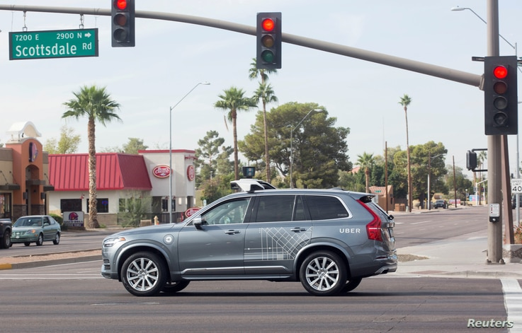 FILE -A self-driving Volvo vehicle, purchased by Uber, moves through an intersection in Scottsdale, Arizona, Dec. 1, 2017.
