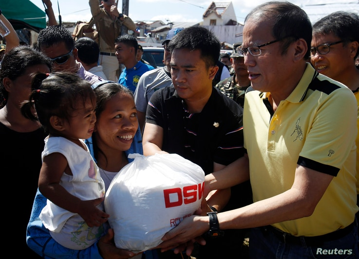 Philippine President Benigno Aquino (R) distributes disaster relief items to survivors of Typhoon Haiyan during his visit to Palo, Leyte province, central Philippines Nov. 18, 2013.