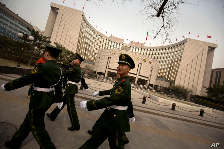 Chinese paramilitary police march past China's central bank, the People's Bank of China, in Beijing, Saturday, March 12, 2016. In a new effort to dispel anxiety about China's cooling economy, the central bank governor said Saturday the country can hi...
