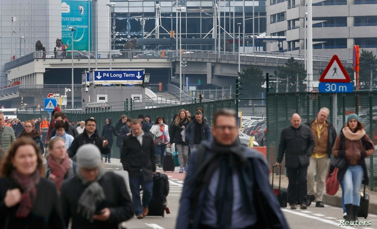 People leave the scene of explosions at Zaventem airport near Brussels, Belgium, March 22, 2016.