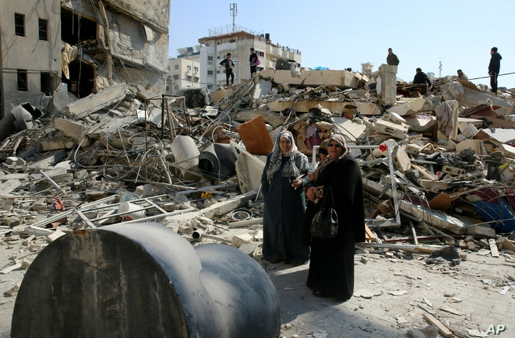 Palestinians search for their family's belongings amid the rubble of destroyed building near a Hamas security building that was destroyed in an Israeli airstrike late Monday, in Gaza City, March 27, 2019.