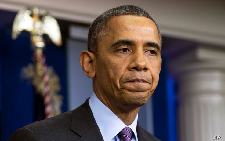 President Barack Obama pauses as he speaks about the death of Nelson Mandela in the briefing room of the White House,  Dec. 5, 2013.