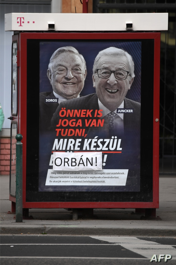 """A poster on a telephone booth shows  EC chief Jean-Claude Juncker, right, and Hungarian-born U.S. investor  George Soros and a slogan reading """"You too have a right to know what Brussels is preparing"""" as the name """"Brussels"""" is covered by the family na..."""