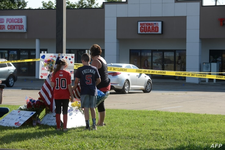 Zach, Zoe and Melissa Cates add to a makeshift memorial near the scene of a shooting at a Armed Forces Career Center/National Guard recruitment office in Chattanooga, Tennessee, July 16, 2015.