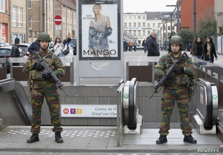 Belgian soldiers keep guard outside a metro station during tensions between police and residents, in the Brussels suburb of Molenbeek, April 2, 2016.