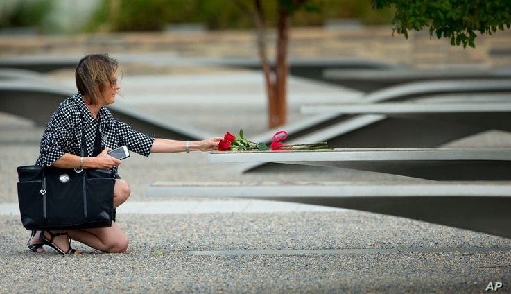 A woman reaches out to touch rose on one of the benches of the Pentagon Memorial at the at the Pentagon, Sept. 11, 2014.
