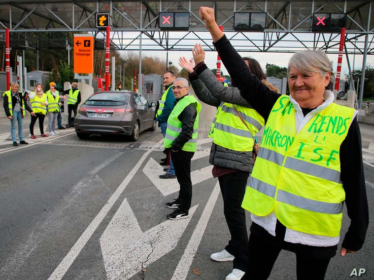 """A demonstrator wearing a yellow jacket reading """"Macron give us the wealth tax"""" protests at the toll gates on a motorway at Biarritz southwestern France, Dec. 5, 2018."""