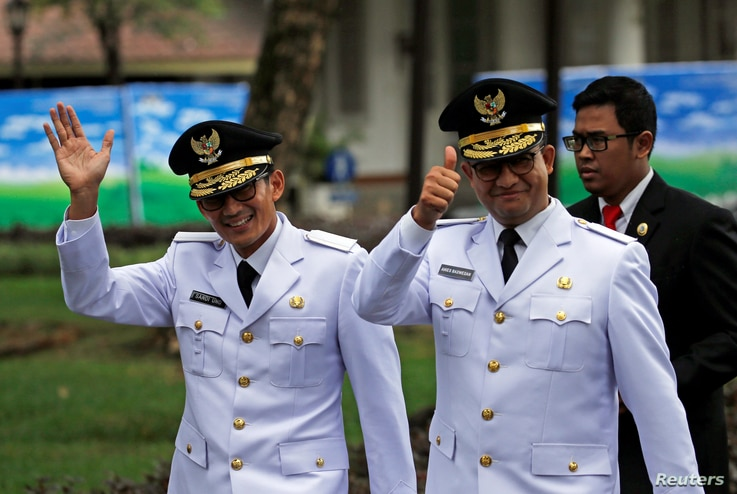 Jakarta Governor Anies Baswedan, right, and his deputy Sandiaga Uno wave to reporters before a swearing-in at the Presidential Palace in Jakarta, Indonesia, Oct. 16, 2017.