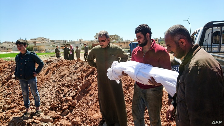 Syrians bury the bodies of victims of a a suspected toxic gas attack in Khan Sheikhun, a nearby rebel-held town in Syria's northwestern Idlib province, April 5, 2017.