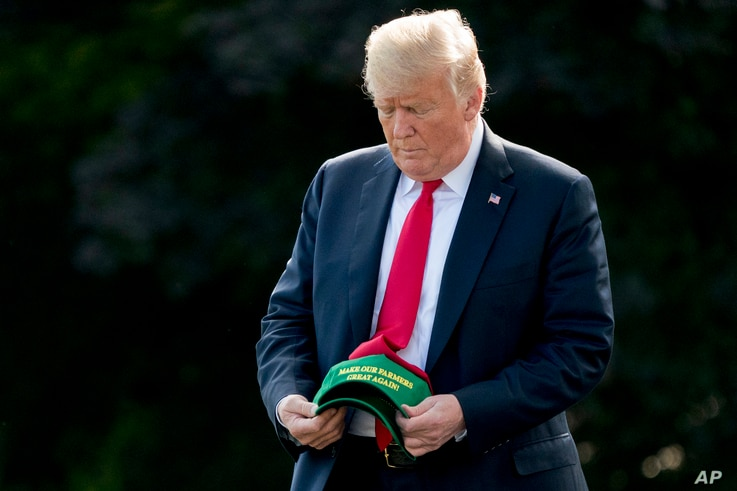"""FILE - President Donald Trump holds a hat reading """"Make Our Farmers Great Again!"""" as he walks across the South Lawn before boarding Marine One at the White House in Washington, Aug. 30, 2018, before heading to a rally in Evansville, Indiana."""