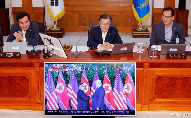 South Korean President Moon Jae-in looks at a TV broadcasting a news report on summit between the U.S. and North Korea during a cabinet meeting at the Presidential Blue House in Seoul, South Korea, June 12, 2018.