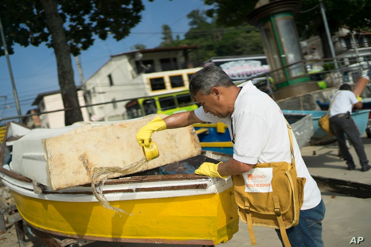 A health agent scoops water from a boat docked at the Jurujuba beach during an operation to eradicate the Aedes aegypti mosquito, in Niteroi, Brazil, March 8, 2016.