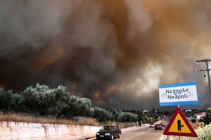 A wildfire burns over the town of Neapoli, southern Greece, July 17, 2015.
