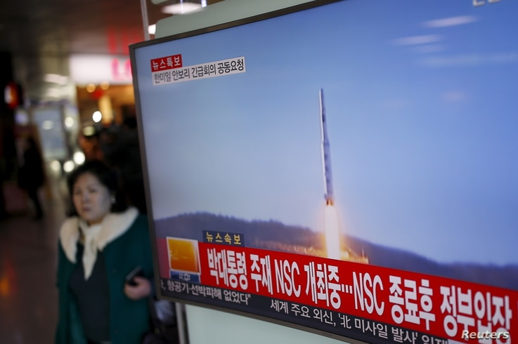 A passenger walks past a TV screen broadcasting a news report on North Korea's long range rocket launch at a railway station in Seoul, South Korea, Feb. 7, 2016.