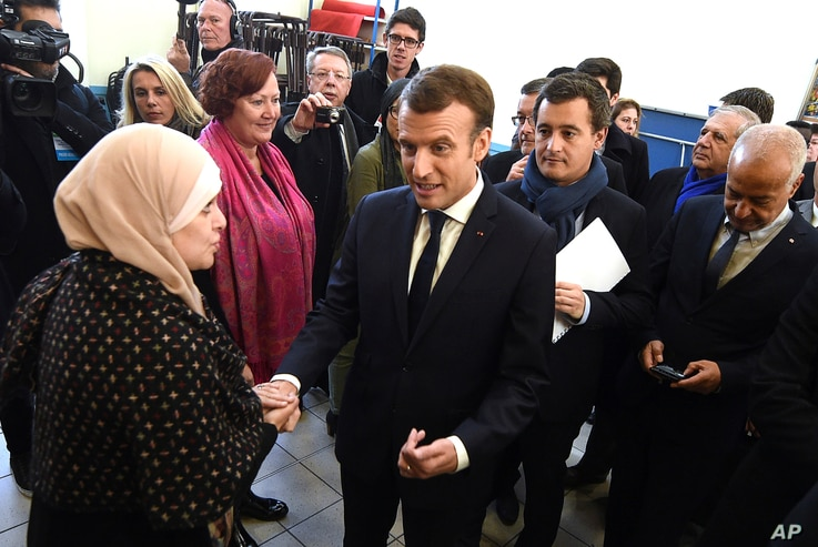 French President Emmanuel Macron shakes hands with a resident next to French Minister of Public Action and Accounts Gerald Darmanin, second right, during a visit to Tourcoing, Nov. 14, 2017.