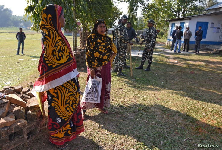 Women stand next to policemen as they wait to check their names on the draft list of the National Register of Citizens (NRC) at an NRC center in Chandamari village in Goalpara district, in the northeastern state of Assam, India, Jan. 2, 2018.