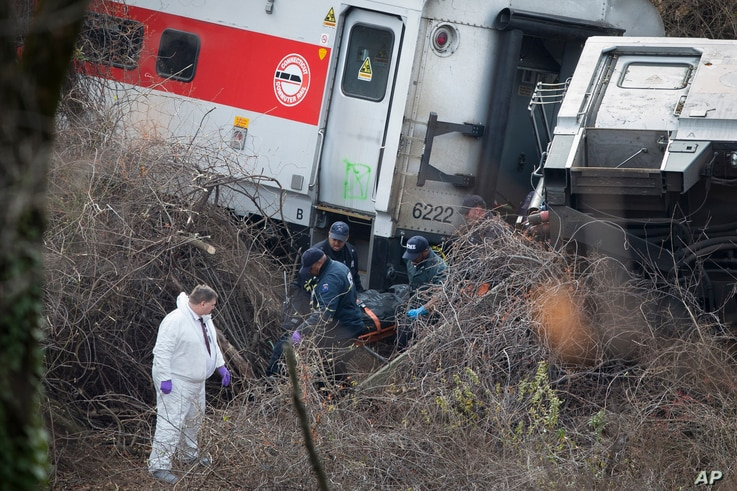 Emergency personnel remove a body from the scene of a Metro-North passenger train derailment in the Bronx borough of New York, Sunday, Dec. 1, 2013. The train derailed on a curved section of track in the Bronx on Sunday morning, coming to rest just i...