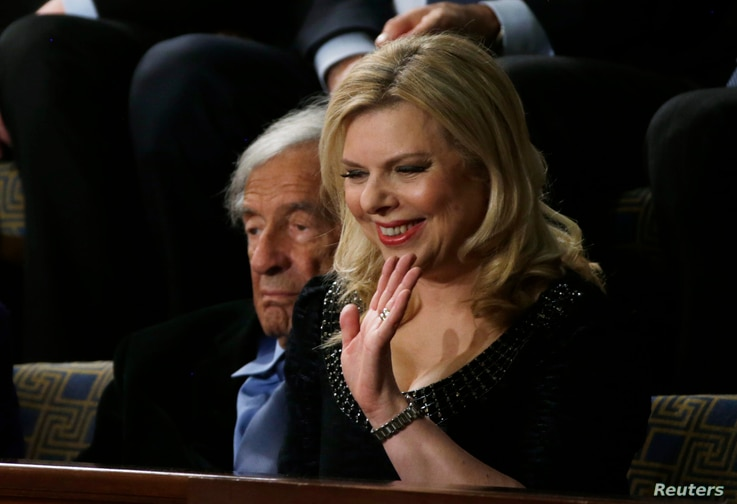 Sara Netanyahu, wife of Israeli Primine Minister Benjamin Netanyahu, waves as she sits next to Holocaust survivor and writer Elie Wiesel (L) in the House Chamber prior to Prime Minister Netanyahu's address to a joint meeting of Congress in the House ...