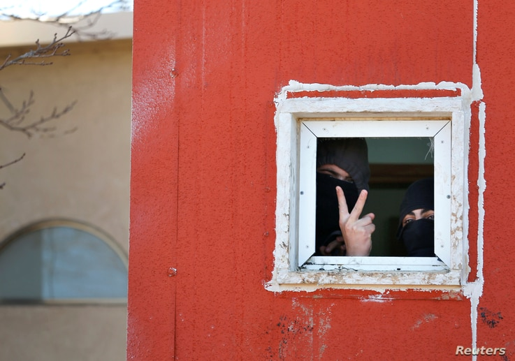 Pro-settlement activists are seen through the window of a house during the second day of an operation by Israeli forces to evict the illegal outpost of Amona in the occupied West Bank Feb. 2, 2017.