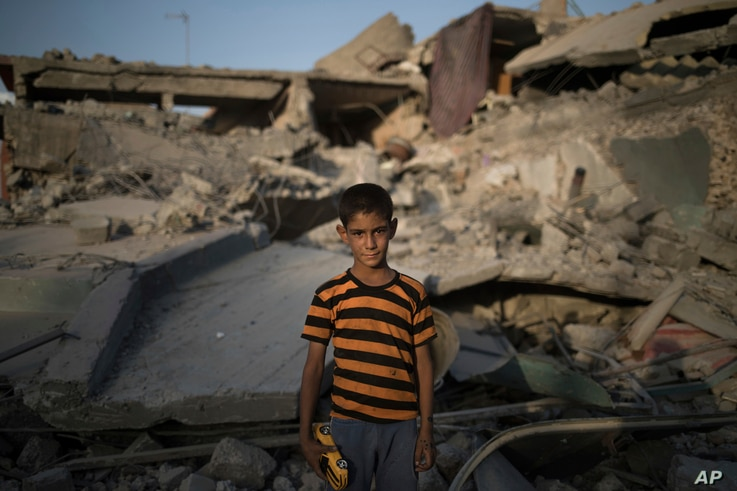 In this July 13, 2017 photo, Ali Mahdi, 9, poses for a photo while playing on his damaged street on the west side of Mosul, Iraq.