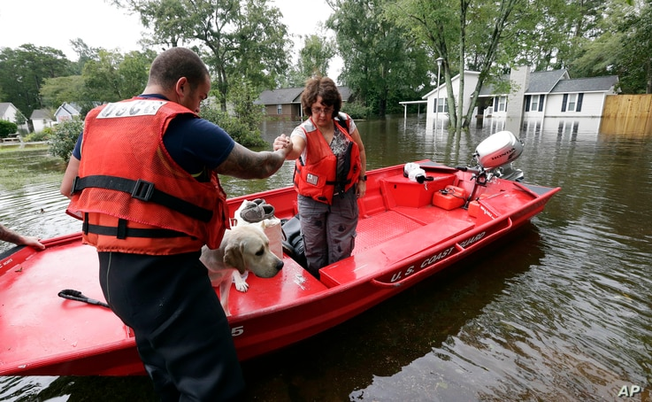 Susan Hedgepeth is assisted along with her dog Cooper by members of the U.S. Coast Guard in Lumberton, N.C., Sept. 16, 2018, following flooding from Hurricane Florence. Hedgepeth was moved to higher ground.