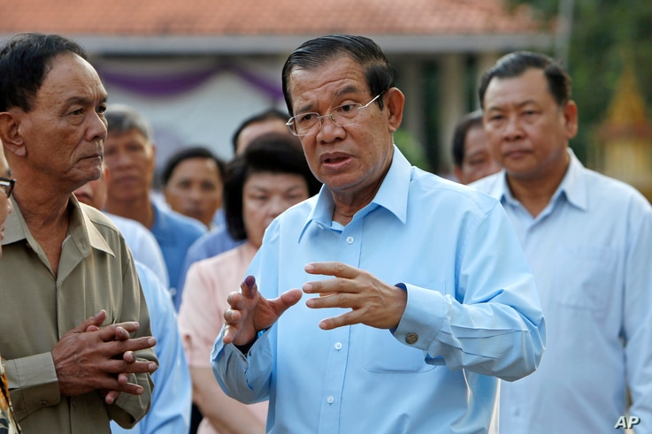 FILE - Cambodian Prime Minister Hun Sen, center, of ruling Cambodian People's Party speaks after voting in the senate election at Takhmau polling station in Kandal province, southeast of Phnom Penh, Cambodia, Feb. 25, 2018.