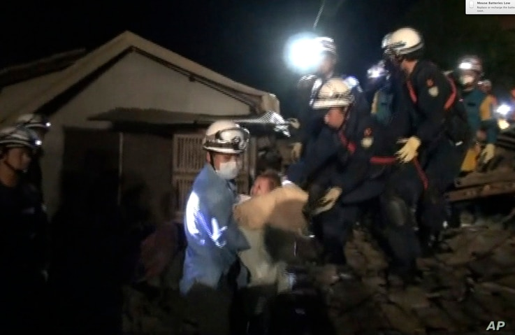 In this image made from video and provided by Kumamoto Prefectural Police, eight-month-old baby Miku Nishimura is carried away after being rescued from her home, which collapsed in a magnitude-6.5 earthquake in Mashiki town, Kumamoto prefecture, sout...