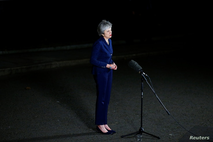 Britain's Prime Minister Theresa May speaks outside 10 Downing Street after a confidence vote by Conservative Party Members of Parliament, in London, Dec. 12, 2018.