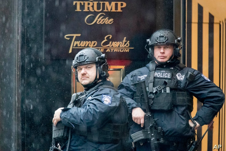 Heavily armed police officers stand guard in the rain outside Trump Tower, Nov. 29, 2016, in New York.