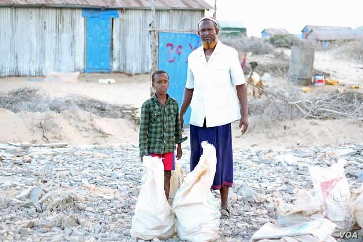 Ibrahim Hassan, with his son, stands where their home stood. Hassan left Dadaab camp in Kenya with his nine children to start a new life in Kismayo, Somalia, Nov. 18, 2016. (M. Yusuf/VOA)
