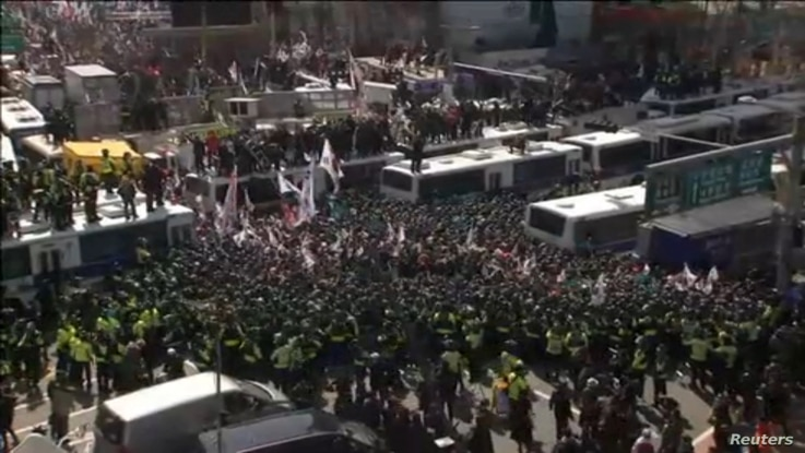 Police surround demonstrators during a protest in front of the Constitutional Court in Seoul, South Korea, in this image from video, March 10, 2017.