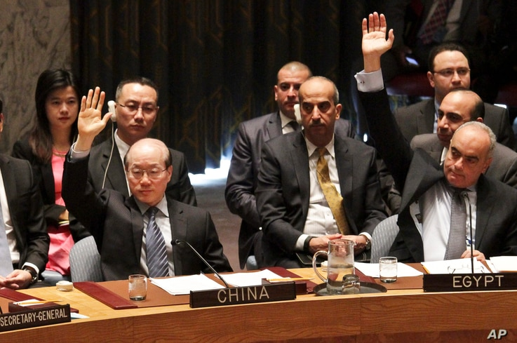 FILE - Chinese ambassador to the United Nations Liu Jieyi, left, and Egypt ambassador to the U.N. Abdellatif Aboulatta, right, vote on a resolution during a Security Council meeting at U.N. headquarters, Wednesday, March 2, 2016.