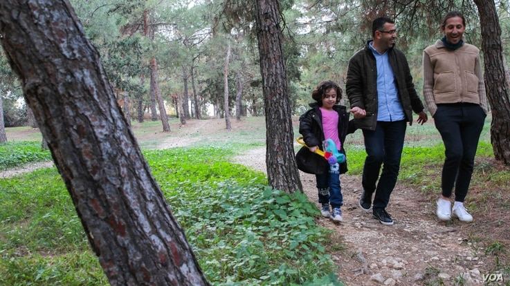 Reham (left), her father Ammar and Adonis walk through their local park.