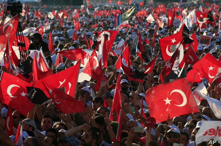 FILE - In this Sunday, July 9, 2017, photo, supporters of Kemal Kilicdaroglu, the leader of Turkey's main opposition Republican People's Party, hold Turkish flags in Istanbul, as they gather for a rally following their 425-kilometer (265-mile) 'March...