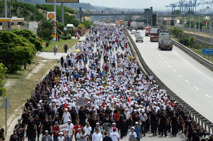 """Kemal Kilicdaroglu, the leader of Turkey's main opposition Republican People's Party, walks with thousands of supporters on the 21st day of his 425-kilometer (265-mile) """" March for justice """" in Izmit, Turkey, July 5, 2017."""