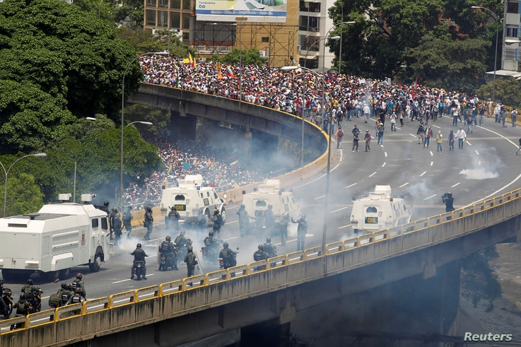 "Demonstrators clash with riot police during the so-called ""mother of all marches"" against Venezuela's President Nicolas Maduro in Caracas, Venezuela, April 19, 2017."