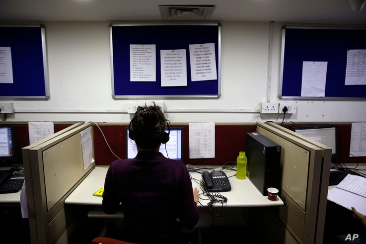 FILE - An Indian woman takes calls on a government hotline established in an effort to confront the country's appalling treatment of women, Dec. 2, 2013..