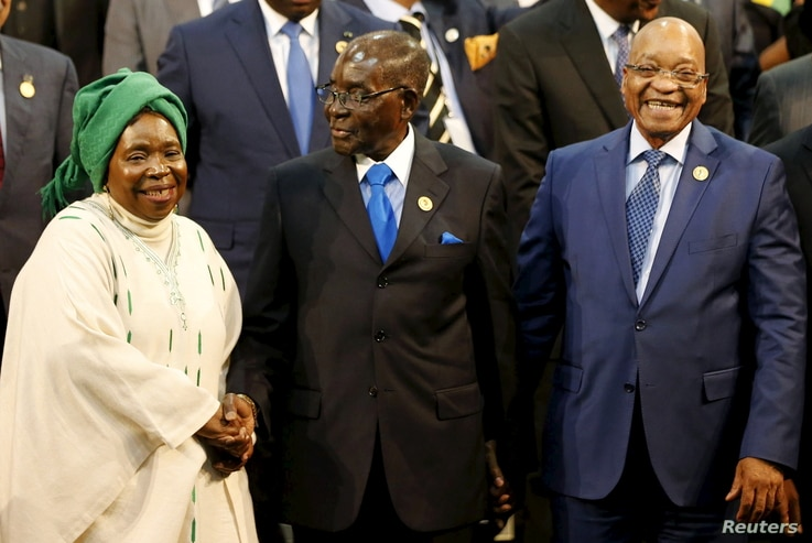 Chairperson of the African Union (AU) Commission Nkosazana Dlamini-Zuma (L) smiles as she is greeted by Zimbabwe's President Robert Mugabe next to South Africa's president Jacob Zuma ahead of the 25th African Union summit in Johannesburg, June 14, 20...
