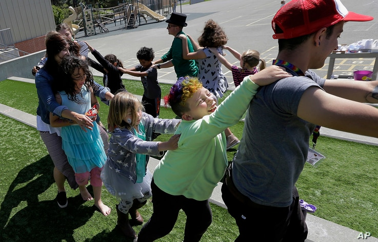 FILE - Campers and camp counselors dance at the Bay Area Rainbow Day Camp in El Cerrito, Calif., July 11, 2017.