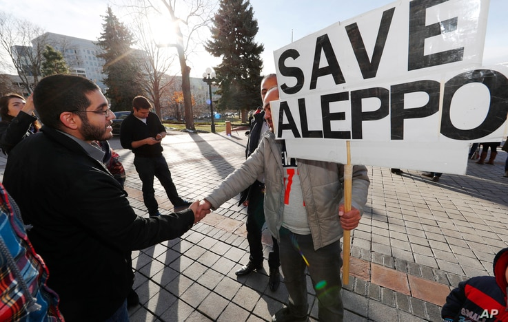 Restaurateur Obeid Kaifo, left, greets a supporter after a protest outside the State Capitol in downtown Denver, Dec. 13, 2016. Protesters joined forces with four state lawmakers calling for the United States to take action to protect the people of A...