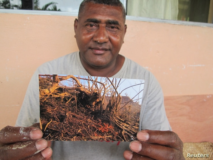 Rupeni Koto holds a photograph of the tree in Nasau, a village on Fiji's Koro island, where his family clung for six hours during Cyclone Winston, the first Category 5 hurricane to hit the South Pacific, Feb. 8, 2018.