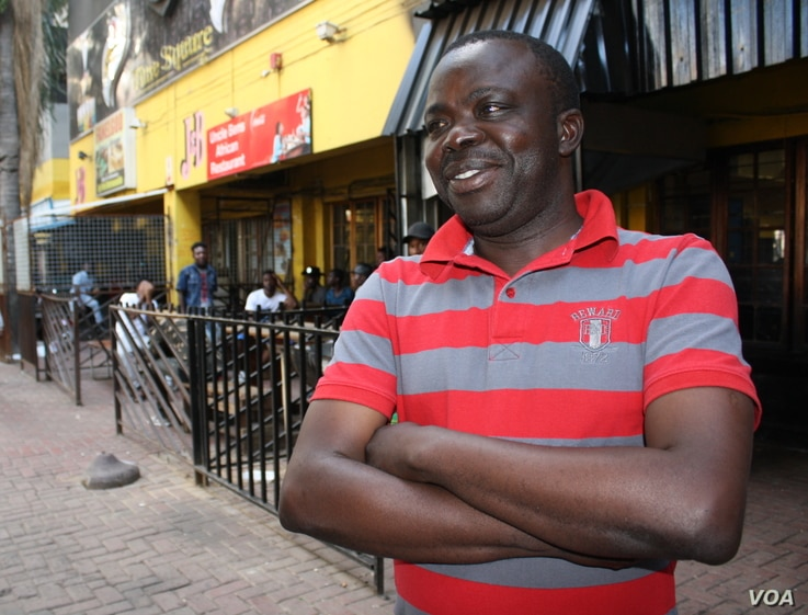 Freddy Lendo, with his Congolese friends in the background, enjoys watching AFCON matches at a bar full of DRC nationals.