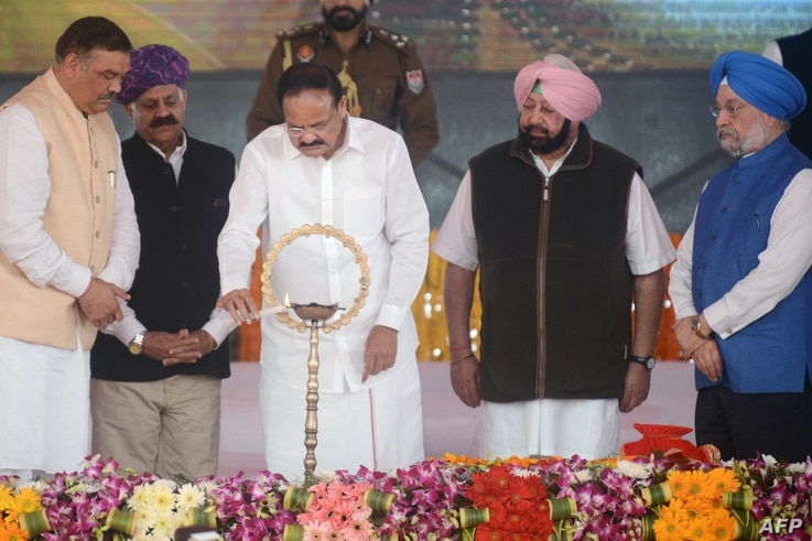Indian Vice President M. Venkaiah Naidu (C), Punjab Chief Minister Amarinder Singh (2R),  Governor of Punjab VP Singh Badnore (2L), and Union Ministers Vijay Sampla (L) and Hardeep Singh Puri (R) light an oil lamp during the foundation stone-laying c...