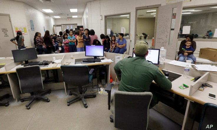 """FILE - U.S. Customs and Border Protection agents work at a processing facility in Brownsville,Texas, June 18, 2014. A new """"surge initiative"""" aims to identify and arrest the adult sponsors of unaccompanied minors who paid smuggling operations to bring..."""